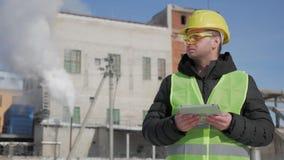 O coordenador no capacete de segurança está usando um tablet pc em uma fábrica da indústria video estoque