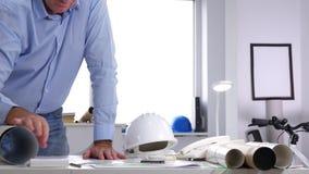O coordenador no escritório faz cálculos técnicos usando a calculadora vídeos de arquivo