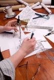 O coordenador, o arquiteto ou o contratante da mulher trabalham em plantas Fotos de Stock Royalty Free