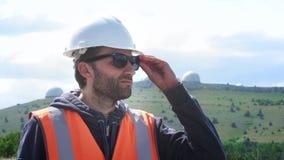 O coordenador ou o construtor masculino em um capacete e em uma veste brancos vestem vidros Contra o contexto de diversos hemisfé video estoque