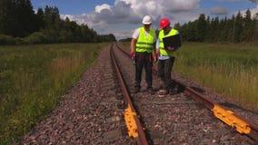 O coordenador Railway com portátil dá instruções para o trabalhador na estrada de ferro filme