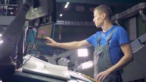 O coordenador trabalha com equipamento industrial usando o écran sensível video estoque