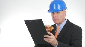 O coordenador Working Take uma ruptura come um sanduíche saboroso e lê da prancheta fotografia de stock
