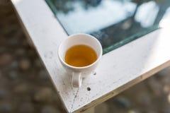 O copo branco derrama o chá verde quente fotos de stock