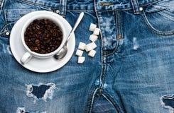 O copo com configuração dos feijões de café, da colher e do açúcar refinado em calças de brim próximo fecha, fundo da sarja de Ni fotos de stock