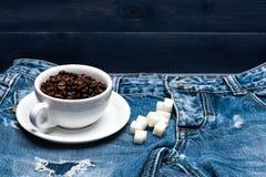 O copo com feijões de café, configuração do açúcar refinado em calças de brim próximo fecha, fundo da sarja de Nimes Conceito fab foto de stock royalty free