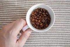 O copo com os feijões de café no fundo cinzento listrou a estrutura fotografia de stock