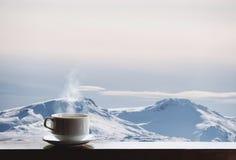 O copo da bebida quente com vapor na mesa e na neve de madeira tampou o Mountain View na manhã fotos de stock