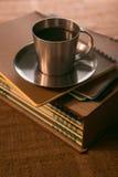 O copo de café com cookies está na pilha de cadernos imagens de stock