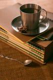 O copo de café com cookies está na pilha de cadernos imagens de stock royalty free