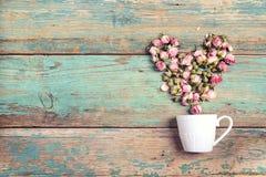 O copo de café com coração da rosa do rosa floresce saindo d sobre Imagem de Stock