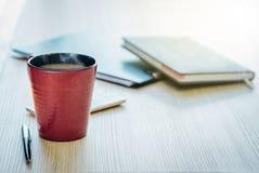 O copo de café do marrom avermelhado está na tabela e na pena de madeira, o d imagens de stock royalty free