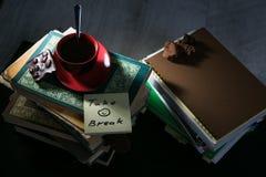 O copo de café e as cookies e as notas do chocolate e do memorando com mensagem na pilha de livros foto de stock royalty free