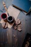 O copo de café e as cookies e o fabricante de café estão na tabela de madeira ao lado do livro fotos de stock