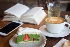 O copo de café e o bolo saboroso relaxam o livro e o telefone celular do tempo em Ta Fotografia de Stock Royalty Free