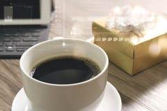 O copo de café e a tabela de Digitas entram o teclado esperto, caixa de presente a do ouro Fotografia de Stock