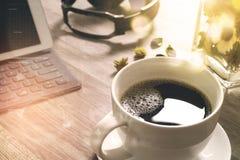 O copo de café e a tabela de Digitas entram o teclado esperto, vaso florescem-na Imagem de Stock