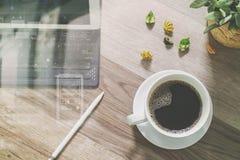 O copo de café e a tabela de Digitas entram o teclado esperto, vaso florescem-na Foto de Stock