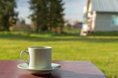 O copo de café está na tabela Fotografia de Stock Royalty Free
