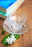 O copo de café na tabela com livros e o jasmim florescem Imagens de Stock