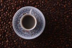 O copo de café quente tradicional com feijões e o fumo cozinham sobre um bla Imagem de Stock