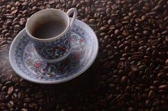 O copo de café quente tradicional com feijões e o fumo cozinham sobre um bla Fotografia de Stock Royalty Free