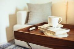 O copo de café registra no descanso de madeira da bandeja da tabela no interior da casa do sofá foto de stock