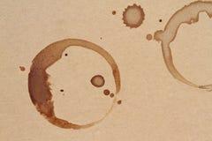 O copo de café soa manchas em uma textura do papel marrom Fotos de Stock Royalty Free