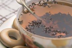 O copo de chá com fim da colher acima, o copo do chá e o bagel estão na toalha de mesa quadriculado Imagem de Stock