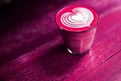 O copo do café do latte das beterrabas está no fundo pintado da tabela Fotografia de Stock