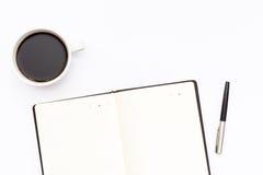 O copo do café preto, abre o diário e a pena em um fundo branco conceito mínimo do negócio Fotografia de Stock Royalty Free
