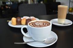 O copo do cappuccino com bolo de chocolate estala no fundo preto Fotos de Stock Royalty Free