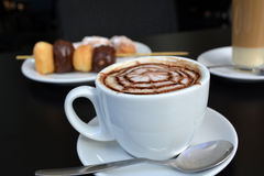 O copo do cappuccino com bolo de chocolate estala no fundo preto Imagens de Stock