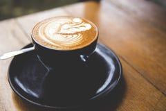 O copo do cappucino quente está na tabela de madeira Imagem de Stock