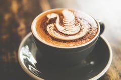 O copo do cappucino quente está na tabela de madeira Imagem de Stock Royalty Free