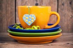 O copo do chá com placas da árvore e do coração manchado deu forma à etiqueta Fotografia de Stock