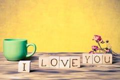 O copo do chá, cubos de madeira e seca flores cor-de-rosa no varrão de madeira novo Imagem de Stock
