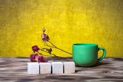 O copo do chá, cubos de madeira e seca flores cor-de-rosa no varrão de madeira novo Fotografia de Stock Royalty Free