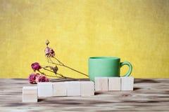 O copo do chá, cubos de madeira e seca flores cor-de-rosa no varrão de madeira novo Imagens de Stock Royalty Free