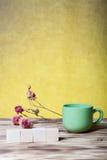 O copo do chá, cubos de madeira e seca flores cor-de-rosa no varrão de madeira novo Imagem de Stock Royalty Free