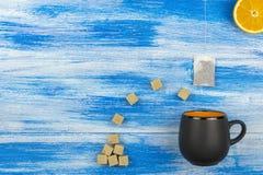 O copo do chá em um fundo azul Saquinho de chá e açúcar e fatias alaranjadas verão Imagens de Stock