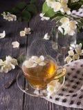 O copo do chá perfumado e o ramalhete do jasmim no vaso no cinza surgem foto de stock royalty free