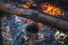 O copo do metal com chá é aquecido da fogueira no inverno foto de stock