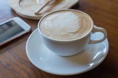 O copo do smartphone quente do anúncio do café pôs sobre o backgrou de madeira velho da tabela Fotos de Stock Royalty Free