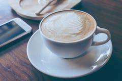 O copo do smartphone quente do anúncio do café pôs sobre o backgrou de madeira velho da tabela Fotografia de Stock Royalty Free
