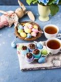 O copo doce da Páscoa endurece treets em shell de ovo coloridos no azul Fotos de Stock