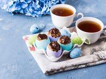O copo doce da Páscoa endurece treets em shell de ovo coloridos no azul Foto de Stock Royalty Free