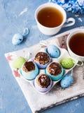 O copo doce da Páscoa endurece treets em shell de ovo coloridos no azul Imagem de Stock Royalty Free