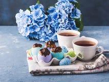 O copo doce da Páscoa endurece treets em shell de ovo coloridos no azul Fotos de Stock Royalty Free