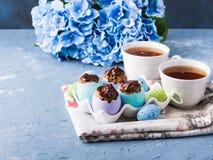 O copo doce da Páscoa endurece treets em shell de ovo coloridos no azul Foto de Stock